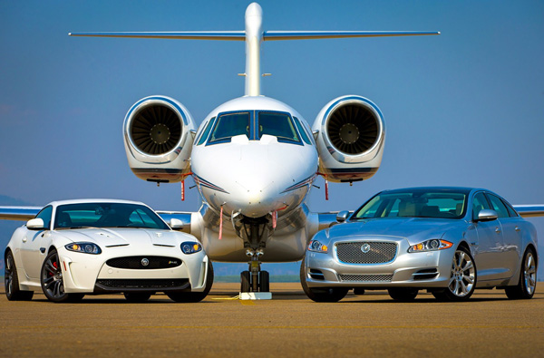 Photo showing head on view of a white car and a silver car parked on either side of a large white twin-engine plane.